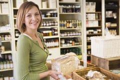 Femme sur le marché regardant le sourire de pain Images libres de droits