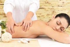 Femme sur le massage de thérapie du dos dans le salon de station thermale images libres de droits