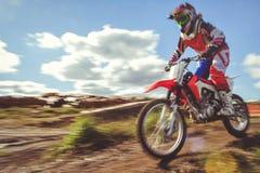 Femme sur le motocross d'enduro dans le mouvement, désir pour la victoire, dynamique de vitesse photographie stock libre de droits