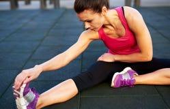 Femme sur le plancher étirant sa jambe Photographie stock libre de droits