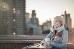 Femme sur le pont de Brooklyn regardant Manhattan avec du café photographie stock libre de droits