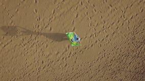 Femme sur le sable avec le drapeau brésilien, tir aérien banque de vidéos