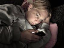 Femme sur le smartphone dans seule l'obscurité Image libre de droits