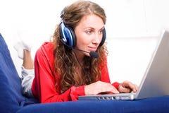 Femme sur le sofa avec l'ordinateur portatif Images libres de droits