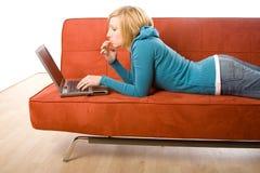 Femme sur le sofa avec l'ordinateur portatif Photos libres de droits