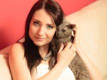 Femme sur le sofa jouant avec le chat Images libres de droits