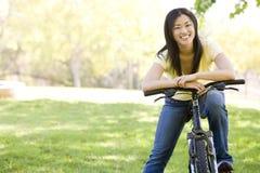Femme sur le sourire de bicyclette Photos stock