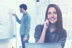 Femme sur le téléphone et un homme dans le bureau Photos libres de droits