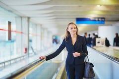 Femme sur le travelator dans l'aéroport international Photo stock