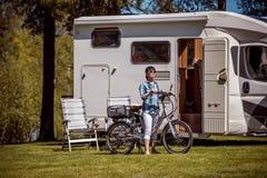 Femme sur le vélo électrique se reposant à la voiture Va de caravane du terrain de camping VR photo stock