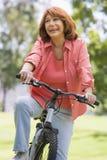 Femme sur le vélo souriant à l'extérieur Photos stock
