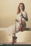 Femme sur le violon se tenant extérieur de pilier Photos stock