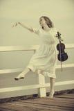 Femme sur le violon se tenant extérieur de pilier Photographie stock