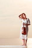 Femme sur le violon se tenant extérieur de pilier Image stock