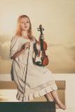 Femme sur le violon se tenant extérieur de pilier Images stock