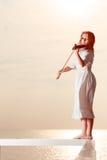 Femme sur le violon se tenant extérieur de pilier Photographie stock libre de droits