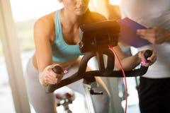 Femme sur le vélo d'exercice au gymnase Photographie stock