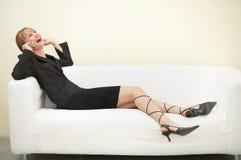 femme sur parler confortable de divan avec le téléphone portable Photo stock