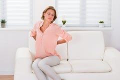 Femme sur Sofa Suffering From Backache photos stock