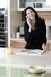 Femme sur son mobile dans une cuisine Images libres de droits