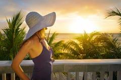 Femme sur un balcon regardant le beau coucher du soleil des Caraïbes Image libre de droits