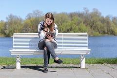 Femme sur un banc avec le comprimé Photographie stock