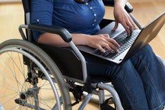Femme sur un fauteuil roulant avec l'ordinateur portable Photographie stock