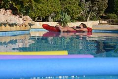Femme sur un lilo dans la piscine images stock
