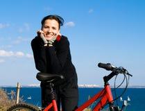 Femme sur un sourire de bicyclette Photos stock