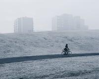 Femme sur un vélo dans le brouillard image libre de droits