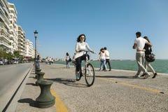 Femme sur un vélo sur l'avenue de Nikis Image libre de droits