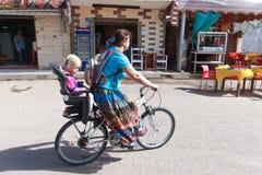 Femme sur une bicyclette avec le descendant Photographie stock