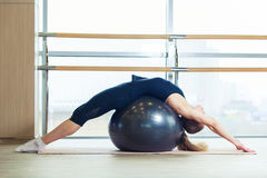 Femme sur une boule de forme physique dans le gymnase Images stock