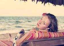 Femme sur une chaise par l'océan avec une fleur dans ses cheveux, rétros Photo libre de droits