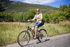 Femme sur une conduite de vélo de loisirs dans les montagnes Photos stock