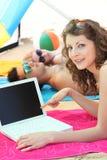 Femme sur une plage avec l'ordinateur portable Images stock