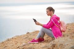 Femme sur une plage rocheuse avec un comprimé au printemps Photographie stock