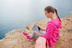 Femme sur une plage rocheuse avec un comprimé au printemps Images stock