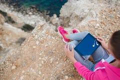 Femme sur une plage rocheuse avec un comprimé au printemps Photos stock