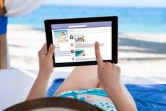 Femme surfant sur le site social à la plage Image stock