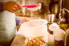 Femme tamisant la farine dans la cuvette Images libres de droits