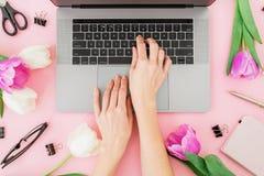 Femme tapant sur l'ordinateur portatif Espace de travail de femme avec les mains, l'ordinateur portable, les tulipes, les accesso Photo libre de droits