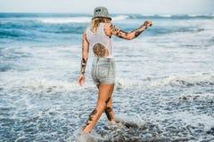 Femme tatouée marchant à la plage Image stock