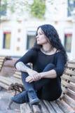 Femme tatouée réfléchie s'asseyant sur le banc Images libres de droits