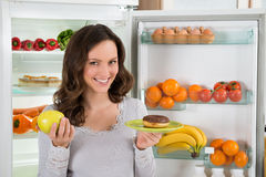 Femme tenant Apple et le beignet verts Photographie stock