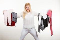 Femme tenant beaucoup l'habillement Photo stock