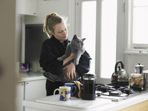 Femme tenant Cat In Domestic Kitchen Photographie stock