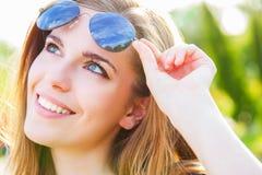 Femme tenant des lunettes de soleil et le sourire Photographie stock