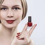 Femme tenant des mains avec une bouteille de vernis à ongles rouge, le rouge à lèvres rouge sur ses lèvres et les ongles rouges Images stock