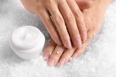 Femme tenant des mains près du pot de crème sur la neige décorative images stock